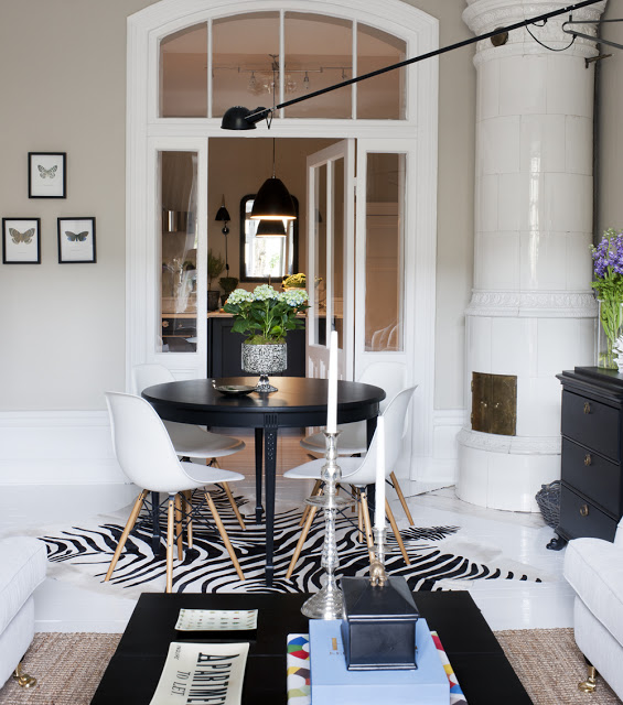 black and white dining space with vintage chairs and zebra carpet