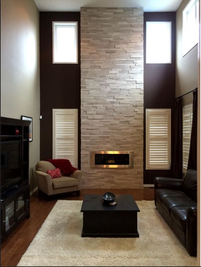 great room with two story stone clad linear fireplace and window shutters