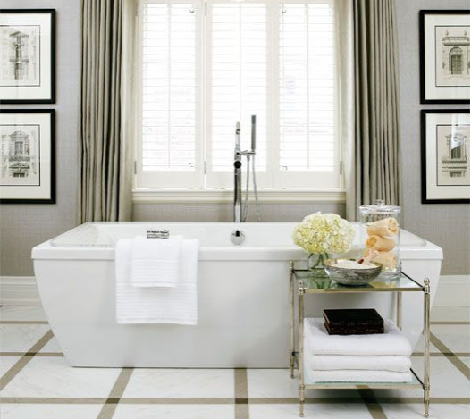 large and formal upscale bathroom with marble tile floor tile, free-standing bathtub, and custom draperies